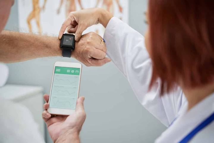 A female doctor checks the smartwatch on the patient hand and compares it to the app on a phone